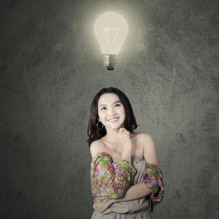 pensamiento creativo: Reflexivo adolescente sonriente feliz mientras mirando lámpara brillante