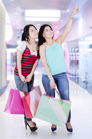 spending full: Portrait of two asian woman with shopping bags standing in the mall and looking at copyspace Stock Photo