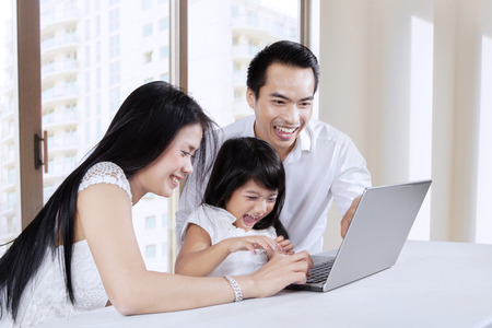 father teaching daughter: Father, mother, and their daughter using laptop together at home Stock Photo