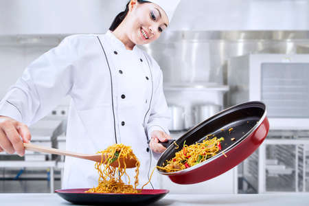 cocinero: Hermosas chef cocina asi�tica fritos fideos en la cocina Foto de archivo