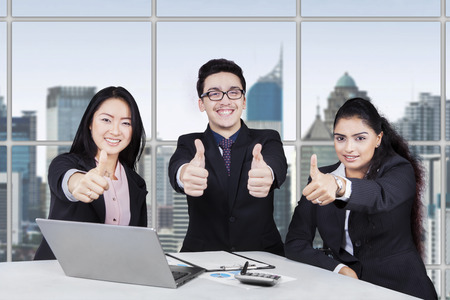 Portrait of happy multi ethnic businesspeople showing thumbs up in a meeting at the office photo
