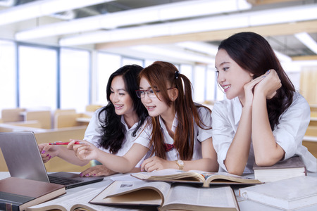 Portrait of lovely three female high school student, studying together in the classroom 스톡 콘텐츠