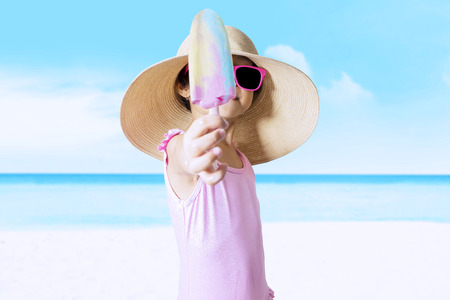 child swimsuit: Closeup of little child with a big hat standing on the beach while wearing swimwear and showing ice cream