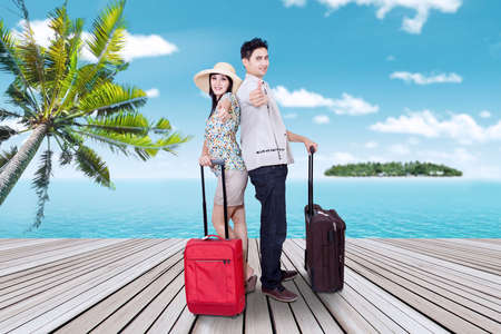 Portrait of young couple arriving at the resort and standing on the pier while showing thumbs up photo