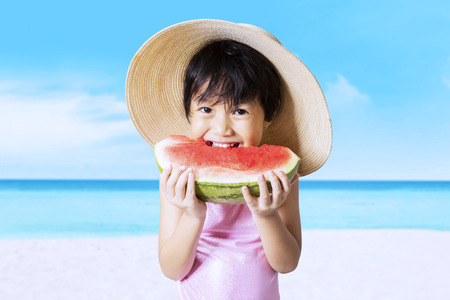child swimsuit: Lovely little girl wearing a hat on the beach while eating a fresh watermelon