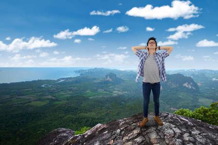persona de pie: Retrato de hombre joven de pie en el borde del acantilado en la montaña mientras se relaja y disfruta del aire fresco Foto de archivo