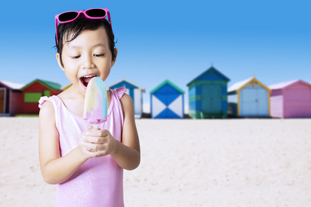 asian bikini: Portrait of cheerful kid standing on the shore while enjoy ice cream and wearing swimsuit