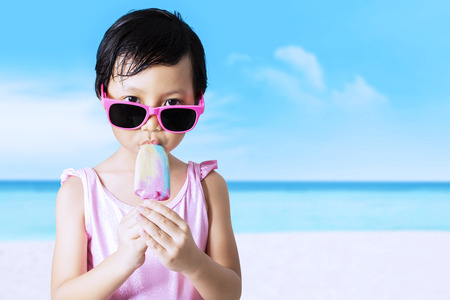 pink bikini: Cute female little child eating ice cream on the coast while wearing swimsuit and sunglasses