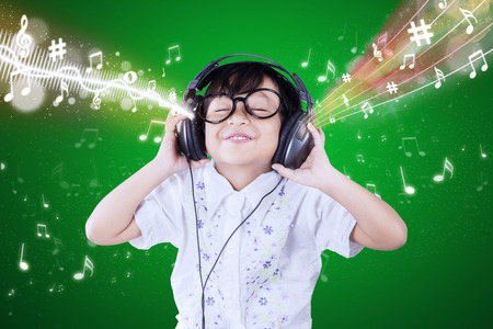 Retrato de la niña linda que usa los auriculares para escuchar la melodía de la música