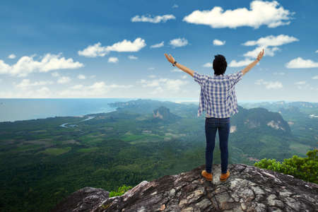 with raised: Rear view of man standing on the cliff edge at mountain peak while raising hands and enjoy fresh air Stock Photo