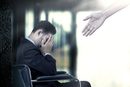 フラストレートしたビジネスマンは車椅子に座って手から助けを得る