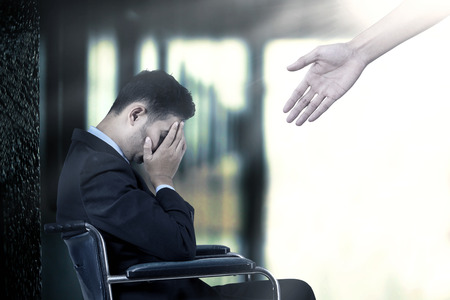 discapacidad: Hombre de negocios frustrado que se sienta en una silla de ruedas, conseguir un ayuda de una mano