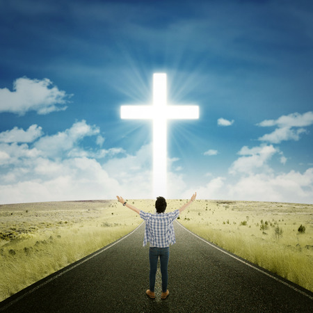 worship god: Rear view of young man standing on the road and raise his hands to worship on the GOD Stock Photo
