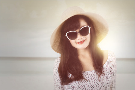 hispanic girl: Portrait of excited woman with sunglasses and hat, standing at the beach