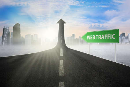 website traffic: Road sign with Web Traffic word, pointing at a road turning into arrow upward symbolizing growing web activity