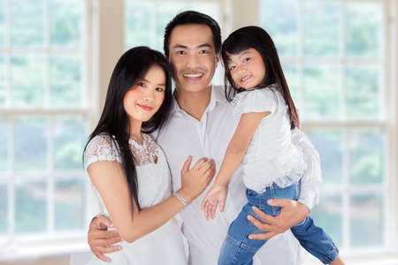 asian family home: Father, mother, and their daughter smiling on camera at home Stock Photo