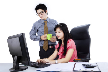 business asia: Two young asian business people using computer on the desk