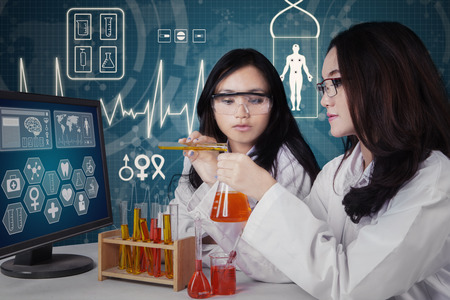 Beautiful schoolgirls doing research and looking at the reaction of chemical liquid in the lab photo
