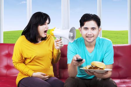 pareja comiendo: Esposa enojada y gritando a su marido en casa Foto de archivo