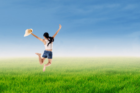 woman wearing hat: Beautiful young woman wearing hat jumping in the grass Stock Photo