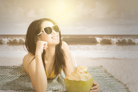 coconut drink: Portrait of pretty model lying on beach while wearing swimsuit and drinking a coconut water