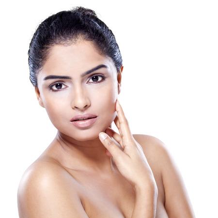 Femme indienne avec beau visage et une peau saine, en regardant la caméra dans le studio, isolé sur fond blanc Banque d'images
