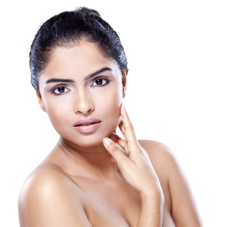 facial cleansing: Indian woman with beautiful face and healthy skin, looking at the camera in the studio, isolated on white background Stock Photo