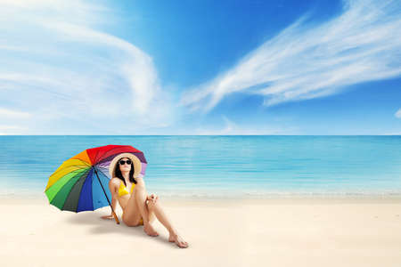 Young woman relaxing on the coast while sitting under colorful umbrella and wearing bikini photo