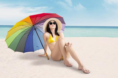 woman umbrella: Pretty woman wearing swimwear and sunglasses, sitting on the sand under colorful umbrella at seaside