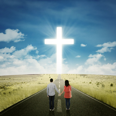 cross road: Rear view of couple holding hands on the highway while looking at a cross on the end of the road