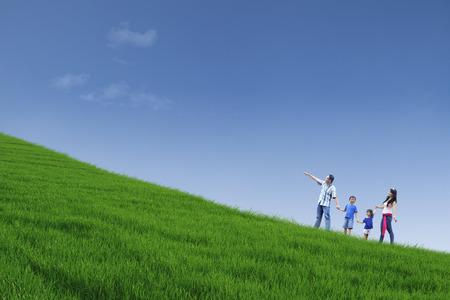 幸せな家族は手を保持しながら緑の野原を歩いてください。