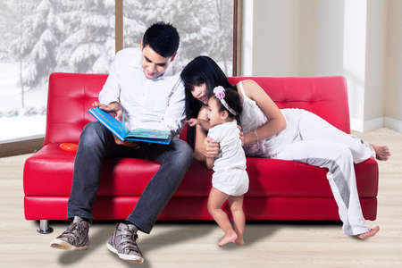 family activities: Young parents read the book to their baby at home