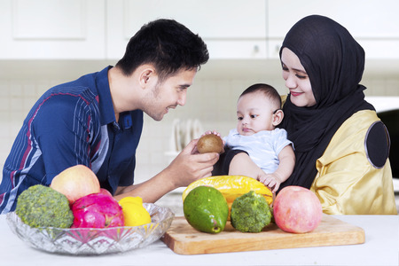 moslem: Portrait of young father with his wife give fresh fruit to his child in the kitchen