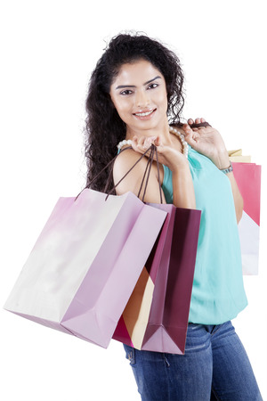 shopaholics: Portrait of beautiful indian woman holding shopping bags while smiling at the camera, isolated on white Stock Photo
