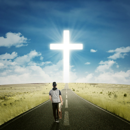 toward: Young guitarist walking on the road while carrying his guitar toward a cross on the end of the road Stock Photo