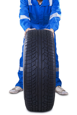 tire repair shop: Mechanic with uniform pushing a black tire to change another tire, isolated on white