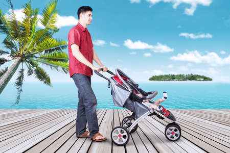 Young father walking on the pier while pushing his baby in the stroller, shot at tropical beach photo