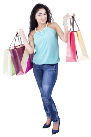 full body woman: Full length of beautiful female model with curly hair and shopping bags, isolated on white background Stock Photo