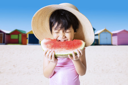 pink bikini: Portrait of asian little girl enjoy a fresh watermelon on the seaside while wearing swimwear and hat Stock Photo
