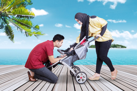 indonesian woman: Portrait of two parents take care their baby in the baby carriage, shot on the jetty at tropical beach