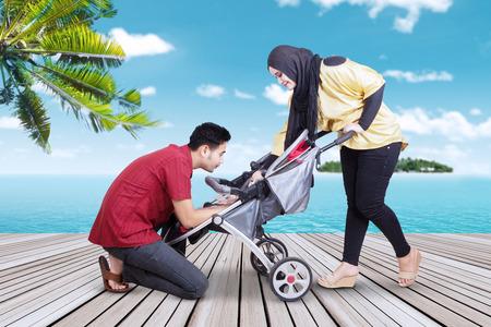 personas de pie: Retrato de dos padres cuidan a su bebé en el cochecito de niño, disparó en el embarcadero en la playa tropical