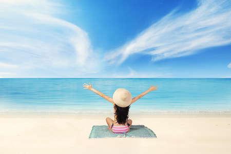 aire puro: Vista trasera de la joven mujer sentada en la costa mientras llevaba bikini y disfrutar del aire fresco Foto de archivo