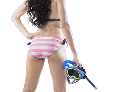 sexy woman panties: Rear view of young woman standing in the studio while wearing swimsuit and holding goggles, isolated on white Stock Photo