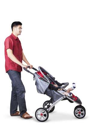 pram: Portrait of happy asian father pushing a baby stroller with his baby inside the stroller, isolated on white background Stock Photo