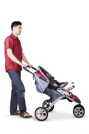niño empujando: Retrato de feliz padre asiático empujando un cochecito de bebé con su bebé dentro de la silla de paseo, aislado en fondo blanco
