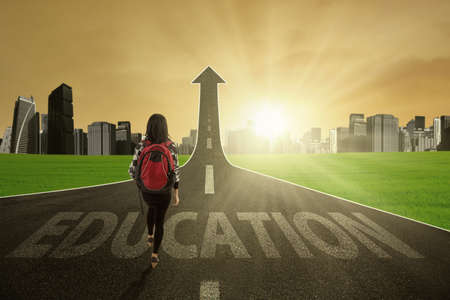 toward: Young schoolgirl walking on the street turning into arrow upward with Education text and bright sunlight