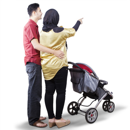Rear view of two parents looking at something in the studio while pushing a baby stroller, isolated on white background Imagens