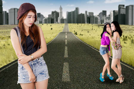 mocked: Depressed teenage girl mocked by her friends and looks sad on the road Stock Photo