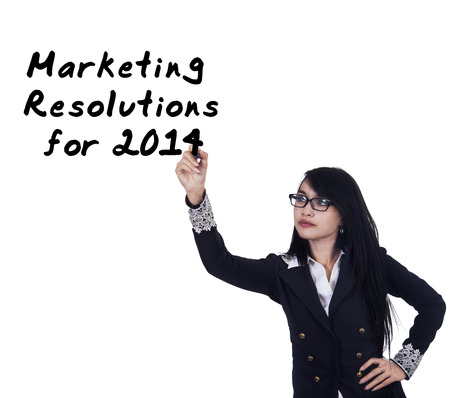 Hispanic business person writes marketing resolutions for 2015 on whiteboard photo