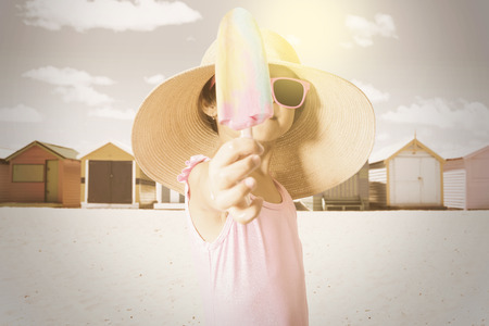 little girl swimsuit: Closeup of little girl showing ice cream on the beach while wearing swimsuit and hat, shot with filter